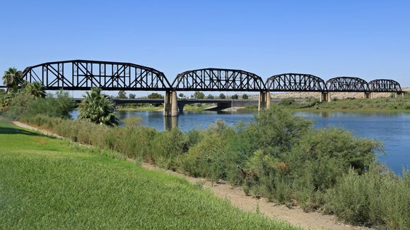 A railroad bridge, foreground, and automobile bridge, background, cross the Colorado River at Parker, Arizona, connecting the Grand Canyon State to California.