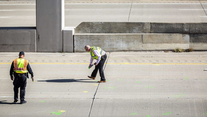 Genesee County Sheriff's officers investigate the scene of a traffic fatality Friday, Oct. 20, 2017, in Vienna Township, Mich.  where Dodge Road crosses Interstate 75. authorities are asking for the public's help in finding out who threw a rock from a highway overpass that smashed a car windshield and killed a 32-year-old man on Oct. 18.