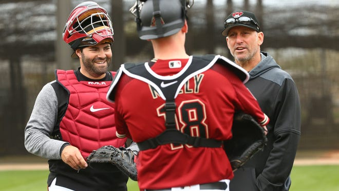 Arizona Diamondbacks manager Torey Lovullo talks with catchers Alex Avila (left) and Carson Kelly (18) during the first day of spring training workouts on Feb. 13 at Salt River Fields in Scottsdale.