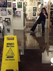 Lauren Patton observes the three inches of standing water in her 5,000-square-foot gallery, ZaPow, on Nov. 18.
