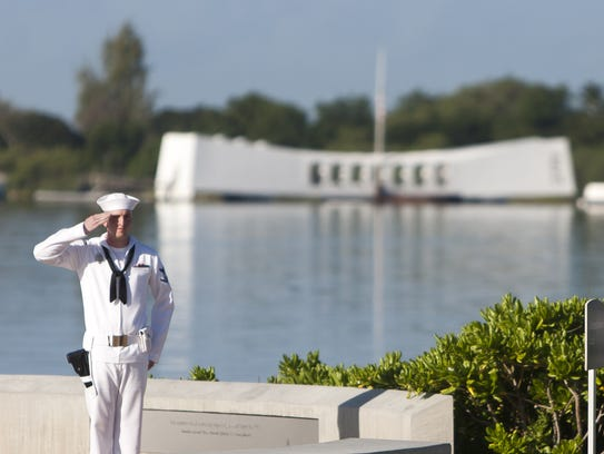 A sailor stands at attention by the USS Arizona memorial