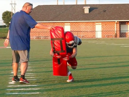 Pequea Valley head coach Mike Choi runs a drill with senior fullback/linebacker Gabe Allgyer during a summer workout.