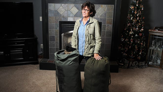 Danine Klinner, of Brandon, S.D., poses for a portrait with two bags of clothing items she collected to give to refugees in Germany Wednesday, Nov. 18, 2015, at her home in Brandon, S.D. Klinner leaves for Germany on Thursday, Nov. 19, 2015, to help refugees. Klinner collected coats, blankets, hats and gloves to hand out to refugees in Germany.