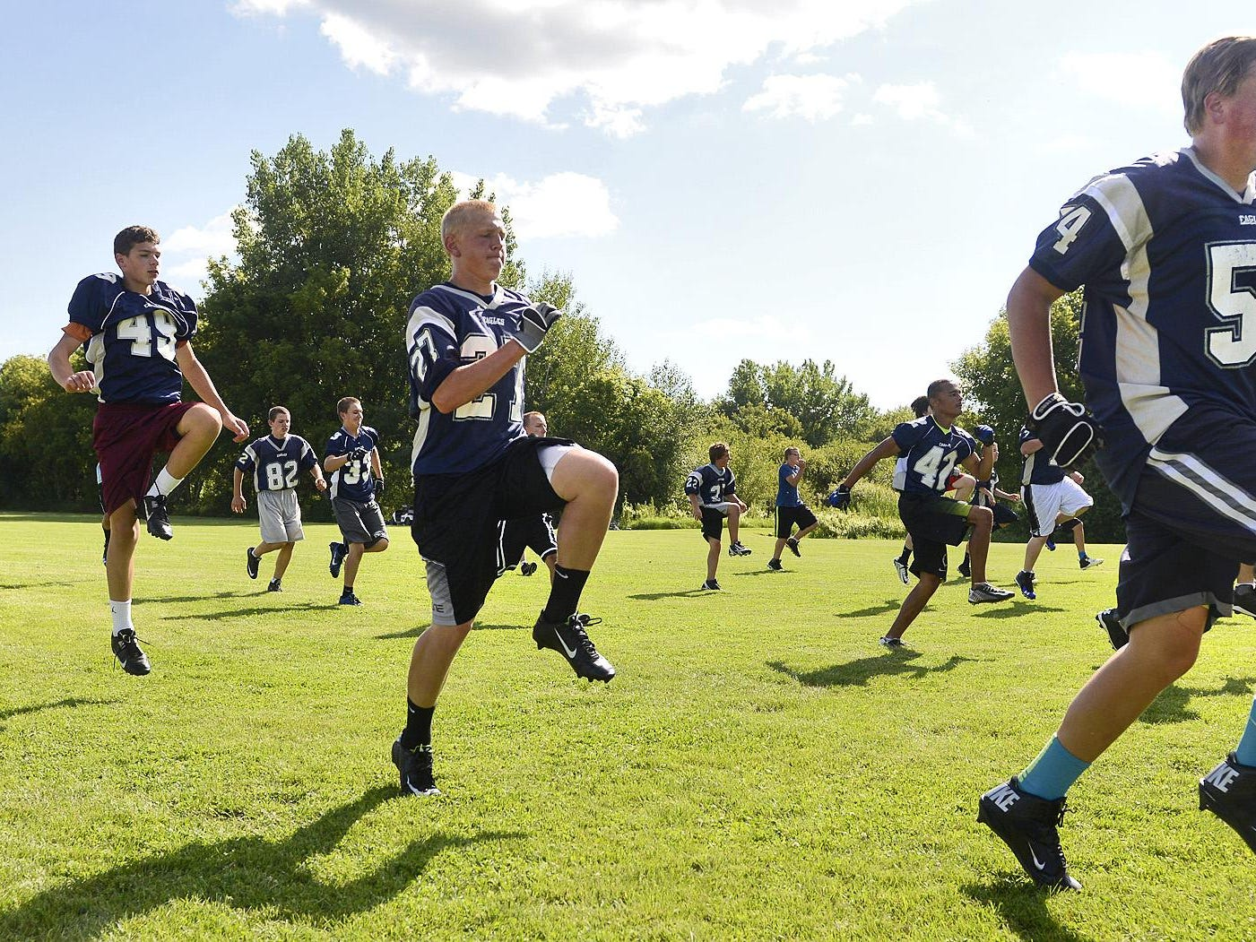 Eden Valley-Watkins players stretch and leap during warmups for practice Aug. 11 in Eden Valley.