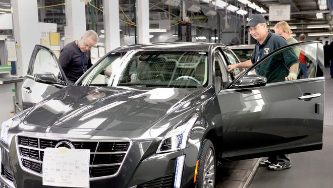 Workers inspect a  Cadillac CTS at Lansing Grand River Assembly in 2014. Roughly 5,300 GM workers in Lansing could receive up to $12,000 in profit-sharing checks this month.