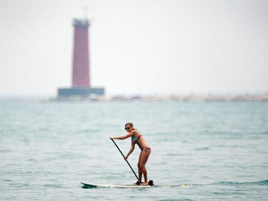 Molly Kubow of Sheboygan paddle boards along Lake Michigan