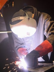 Student Joe Livington, 25, welds at Cincinnati State Technical and Community College. The school will open a new 12-booth welding lab at its Clifton campus.