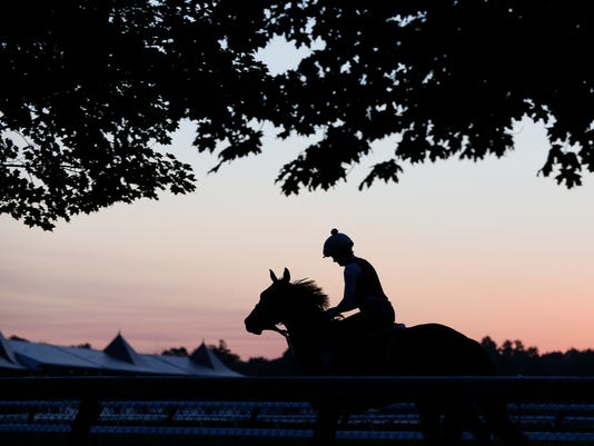 An exercise rider rides a horse during morning workouts at Saratoga Race Course on Thursday, July 21, 2016, in Saratoga Springs, N.Y. The Saratoga thoroughbred racing season opens Friday. (AP Photo/Mike Groll)
