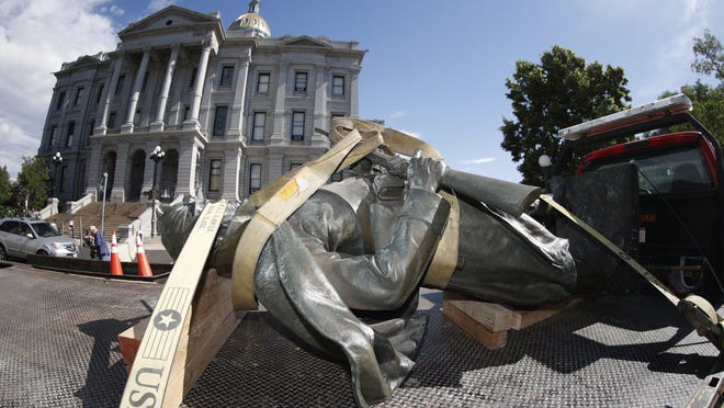 The Civil War Monument statue is strapped on the back of a flatbed tow truck after it was toppled from its pedestal in front of the State Capitol, June 25 in Denver.