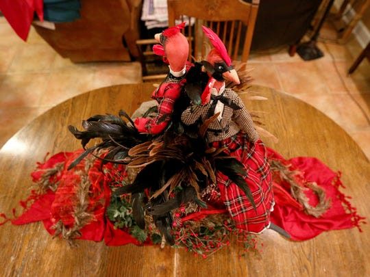 Tass Morrison's table centerpiece was created with scarves, feather boas, berry garland, feathers and a vase sitting in a wreath.