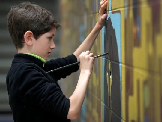 Under the direction of artist Chad Brady, third grade student Donald Voetberg helps paint a mural on a wall at Columbus Elementary School on Thursday, June 1.