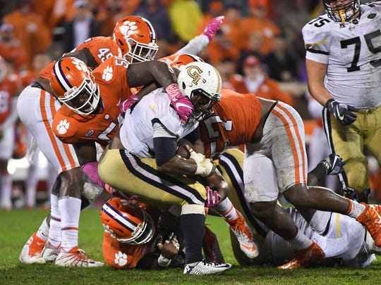 Clemson offensive lineman Jabril Robinson (50) and linebacker Tre Lamar (57) tackle Georgia Tech quarterback TaQuon Marshall(16) during the third quarter in Memorial Stadium at Clemson on Saturday.