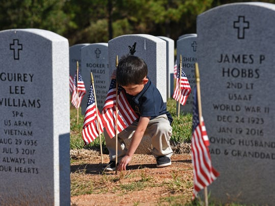 Cooper Heiderich places flags on the graves of local
