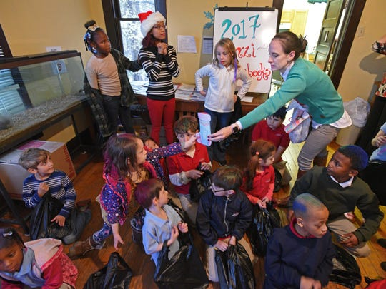 Executive Director Christie Rodriquez hands out presents at the Renzi Education and Art Center 2017 Christmas party.