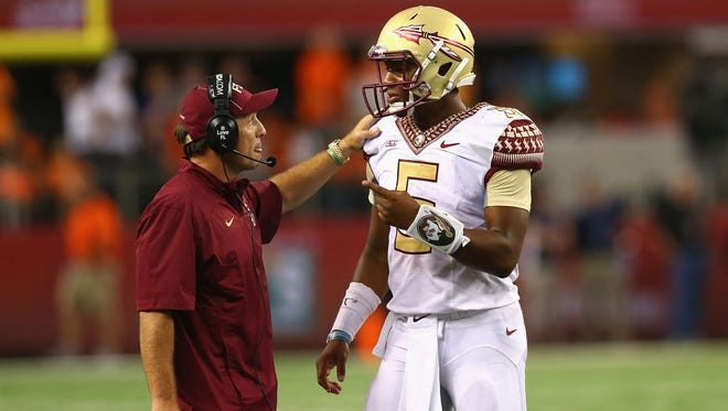 Florida State coach Jimbo Fisher (left) talks with Jameis Winston (5) in the fourth quarter of play against the Oklahoma State Cowboys at AT&T Stadium.