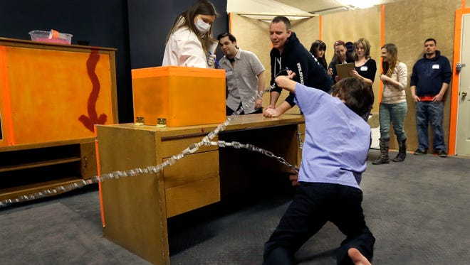 "A chained zombie reaches for participants as they play ""Trapped in a Room With a Zombie."" Up to a dozen people are locked in a room for an hour alongside a zombie that's chained to a wall. Every five minutes, a buzzer sounds, and the zombie is given another foot of chain, allowing the undead creature to scamper even closer to its next meal. If participants don't solve a series of puzzles within the 60 minutes, the zombie ""eats"" everyone in the group. (AP Photo/Carlos Osorio)"