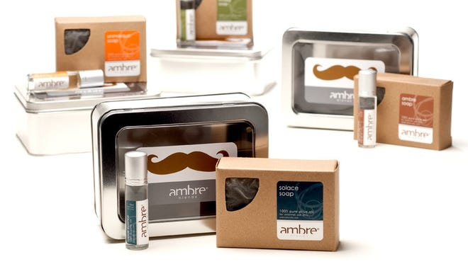 "These ""Stache Sets"" from Ambre Blends include a reusable tin with olive oil soap and ""roll-on essence"" inside. Of course, the tins also feature a mustache on the windowed tin. They're available for $65 online only through June 15 at ambreblends.com."