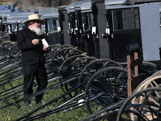An Amish man looks over one of the many buggies offered up for auction during a mud sale in Gordonville, Pa., on Saturday, March 10, 2018. The annual event, which helps raise money for volunteer fire companies, offers indoor and outdoor auctions, selling items from buggies and farm equipment to horses.