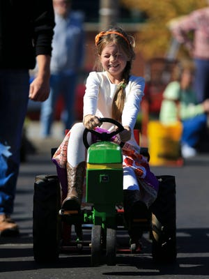 Lacy Schilmiller give it her all as she competes in the kid tractor pull at the Harvest Homecoming Saturday morning.