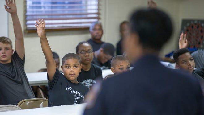 Hands go up for questions during a meeting of Young Men, Inc., youth ministries, Indianapolis, Tuesday, July 11, 2017. The children are asking questions from an IMPD recruiter who's answering questions about what it's like being part of the police force.