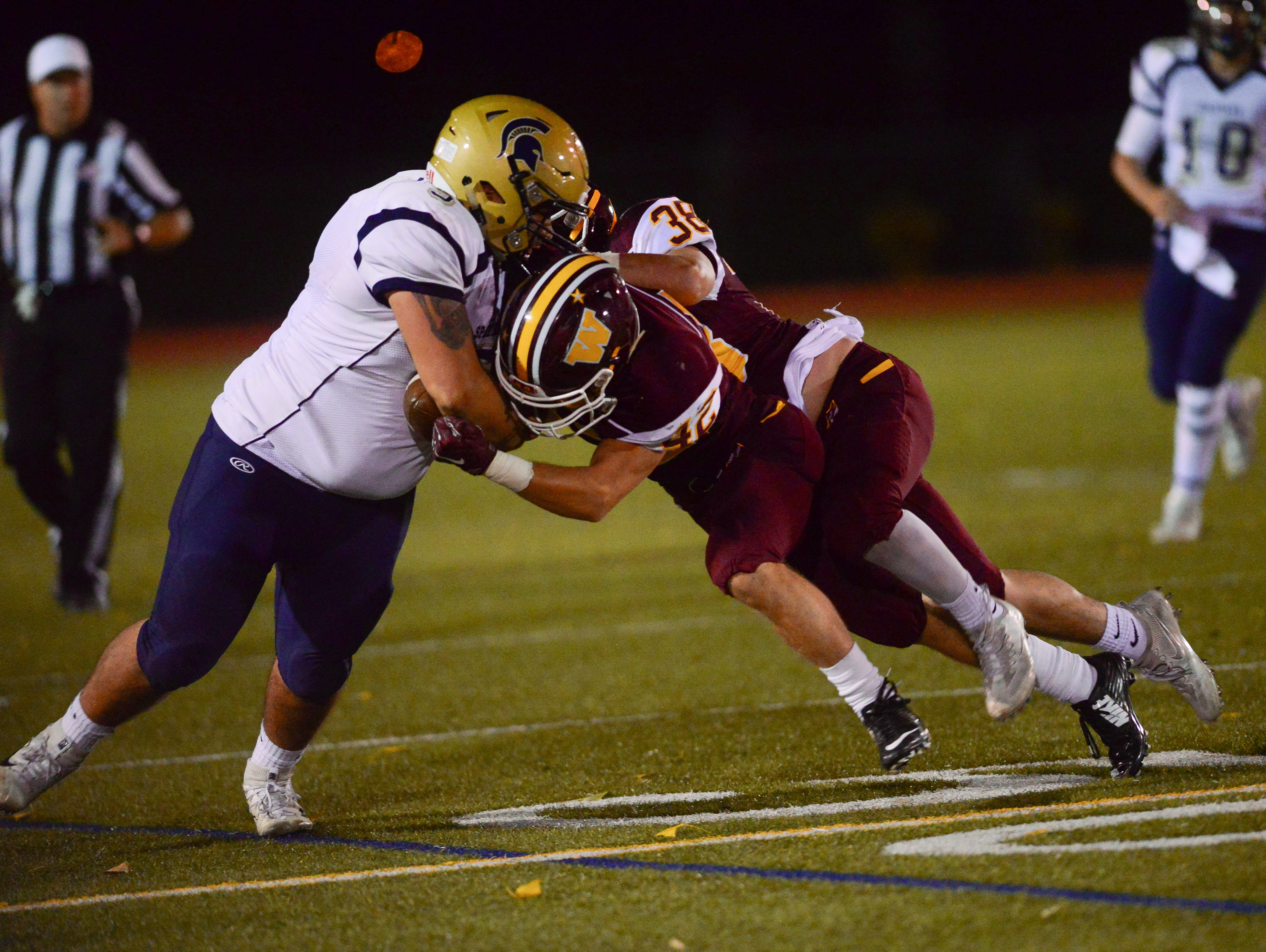 Windsor linebackers Tony Carr and Nate Cole take down Greeley fullback Devin Sirio during the game at Windsor High School Friday, September 23.