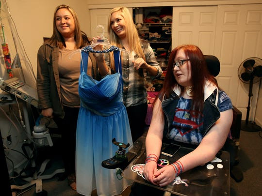 Caregivers Cassandra Zeller (left) and Nakeisha Cheever (center) hold the prom dress McKensie Teal of Salem will wear to her boyfriend's senior prom in Georgia. Driving across country will be challenging for McKensie because of her physical challenges and medical needs.