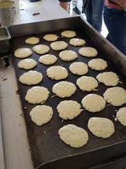 A griddle full of pancakes cooks Monday at Oñate High