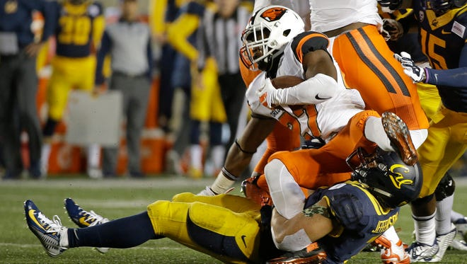 Oregon State cornerback Naji Patrick is brought down with the ball by California linebacker Jalen Jefferson, bottom, during the first half of an NCAA college football game Saturday, Nov. 14, 2015, in Berkeley, Calif.