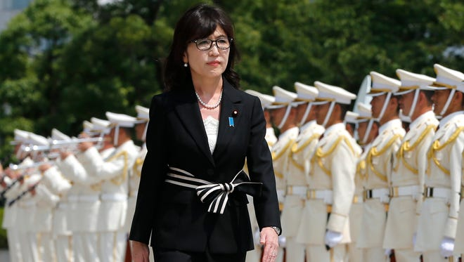 Japan's new Defense Minister Tomomi Inada inspects an honor guard on her first day at the Defense Ministry in Tokyo on Aug. 4, 2016.