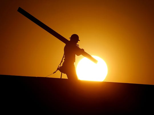 A home builder works at sunrise, Monday, June 20, 2016, in Gilbert, Ariz., in an effort to beat the rising temperatures. The National Weather Service is expecting another day of triple-digit temperatures in Phoenix and across much of the Southwest. The mercury reached 118 on Sunday, breaking the record of 115 set nearly 50 years ago. The heat played a role in the deaths of mountain biker in Phoenix and a hiker in Pinal County over the weekend.