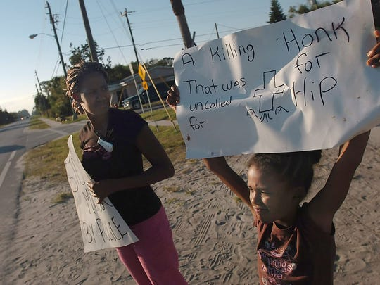 Shameika Northern (left), of Gifford, and her daughter, Natasia Faust, 8, both cousins of Byruss Green, who killed by an Indian River County Sheriff's deputy on Nov. 9, 2007, hold signs with other family members and friends on Nov. 21, 2007, to gain support over what they feel is a wrongful death by the Sheriff's Office. They were on the corner of 45th Street and 33rd Avenue in Gifford for a third day to protest Green's death.