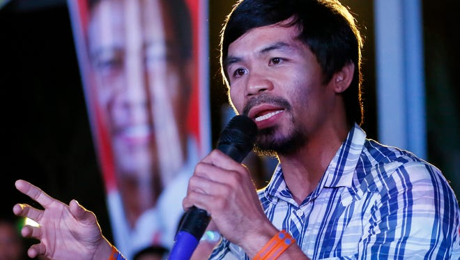 Boxing star Manny Pacquiao addresses supporters as he campaigns for a seat in the Philippine Senate, on Thursday, April 28, 2016 at San Pablo city, Laguna province south of Manila, Philippines. Pacquiao had few visible security escorts as he campaigned in Laguna province, shaking hands and allowing mobs of villagers to take selfies with him despite a reported militant plot to kidnap him. (AP Photo/Bullit Marquez)