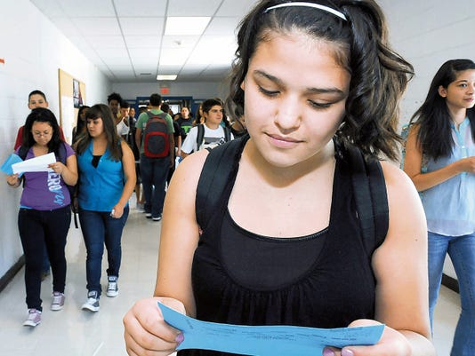 Las Cruces High School freshman Ashley Marquez, 14, takes a long look at her class schedule on the first day of school in August of 2013, while students buzz past her in the school hallway during the first day of classes.