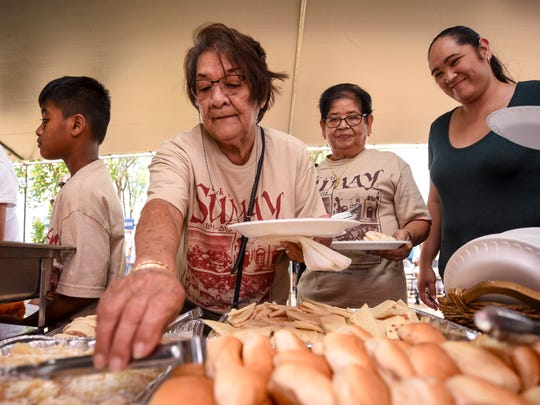 Former Sumay resident Chong Cruz prepares herself a plate of food as she partakes in a fiesta-style layout during the 9th annual Back to Sumay Day event on Saturday, April 7, 2018. A Mass was celebrated for those in attendance, as well as a feast of local foods, music, cultural dancing and a display of photos dating back to pre-World War II Sumay. Sumay was once a small fishing village which evolved into an agricultural and commercial hub for ships in the mid-1800s, before becoming an economically rich village by the 1930s.