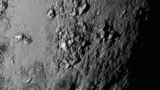 In this handout provided by NASA, a close-up image of a region near Pluto's equator shows a range of mountains rising as high as 11,000 feet, taken by NASA's New Horizons spacecraft as it passed within 7,800 feet of the dwarf planet on July 14, 2015.