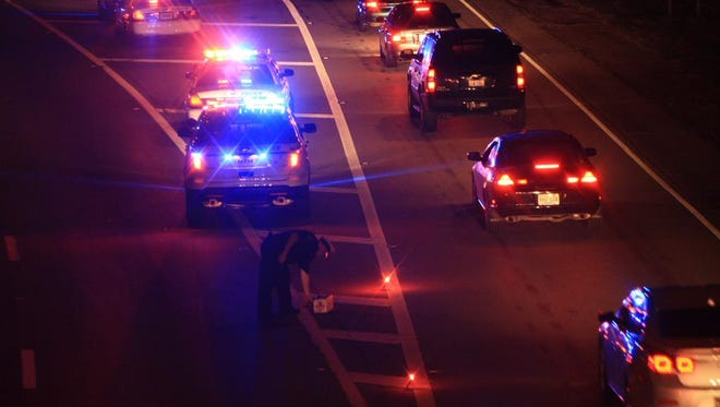 A Cincinnati police officer sets up flares to help divert traffic from the scene of a reported shooting on I-75.