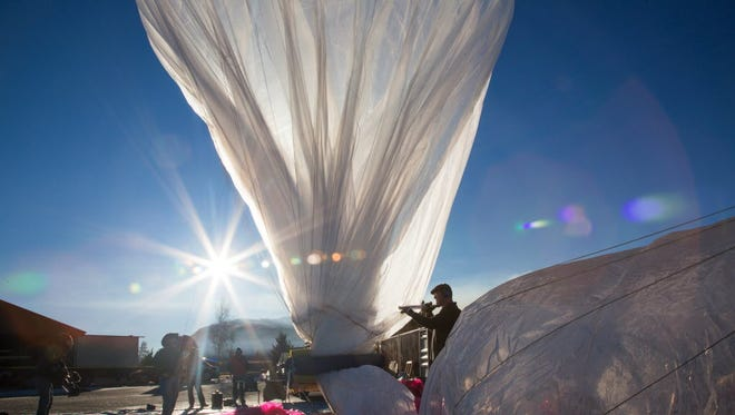 Project Loon team member Bill Rogers fills a balloon with helium while Paul Acosta monitors inflation in this 2013 file photo.
