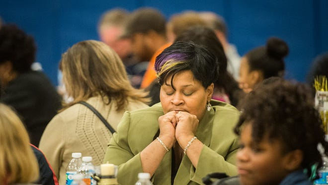 Tandrea Roper bows her head in prayer during the 2015 MLK event titled Where Do We Go From Here? This year's event will be at 4 p.m. Jan. 17 at Lincoln Charter School in York.