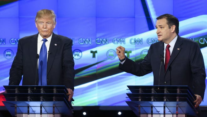 Donald Trump listens as Ted Cruz answers a question during the Republican presidential debate in Houston on Feb. 25, 2016,