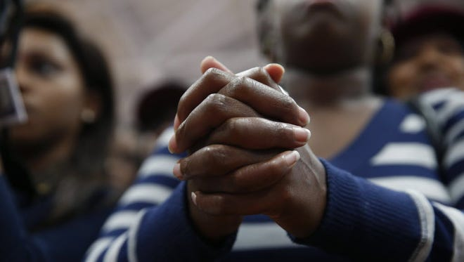 """A supporter clasps her hands as she listens to Democratic presidential candidate Hillary Clinton speak at a """"Get Out the Vote"""" rally for historically black colleges and universities, at South Carolina State University in Orangeburg, S.C., on Feb. 26, 2016."""