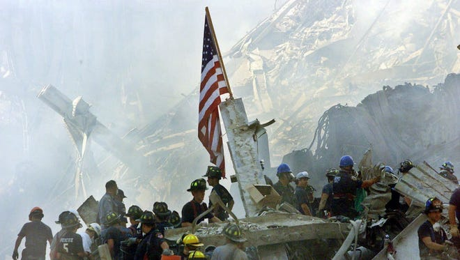 In this Sept. 13, 2001, file photo, an American flag flies over the rubble of the collapsed World Trade Center buildings in New York.