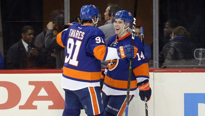 Islanders defenseman Thomas Hickey (14) celebrates his game-winning goal in overtime against the Flames with center John Tavares (91).