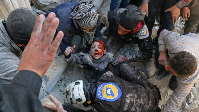 White Helmets rescue a boy in Aleppo, Syria, last month.