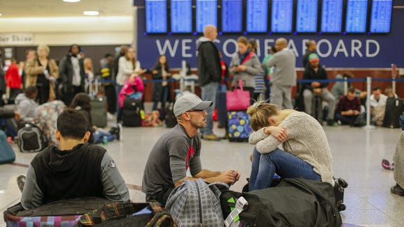 Stranded Delta Air Lines passengers wait Jan. 29, 2017,