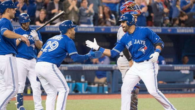 The Blue Jays' Jose Bautista, right, celebrates with teammate Devon Travis, left, after Bautista's three-run home run in the fifth inning against the Rangers at Rogers Centre in Toronto.
