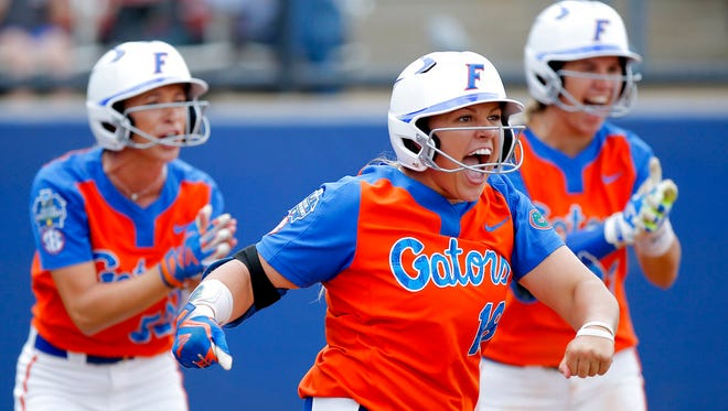 Florida's Amanda Lorenz (18), Justine McLean (52) and Nicole DeWitt (23) celebrate a score in the second inning during the Women's College World Series softball game against Washington in Oklahoma City, Sunday, June 4, 2017.