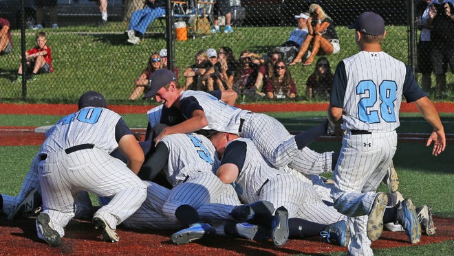 West Bend West players pile on each other after the Spartans beat Menomonee Falls, 7-2, in the Whitefish Bay sectional final on Monday to earn a bid to the WIAA state summer baseball tournament.