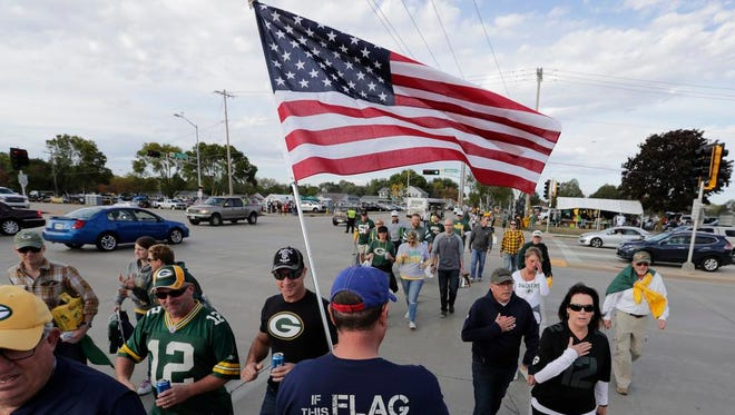 """Green Bay Packers fan Tom of Appleton carries a flag and reminds people to have their hands over their hearts during the national anthem Thursday, Sept. 28, 2017, prior the the game against the Chicago Bears at Lambeau Field in Green Bay, Wis. """"The flag isn't representing racism, the flag is representing freedom and the blood shed for that freedom. Kneeling is for prayer and sitting on the bench is for after you've played and you need a rest."""""""