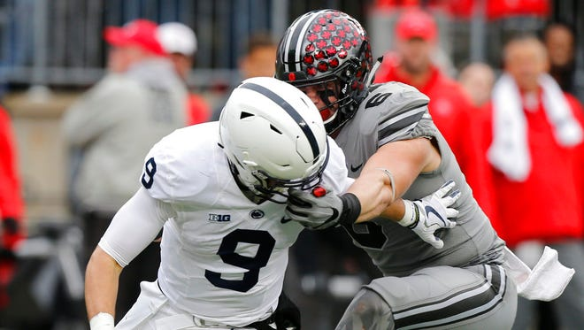 Ohio State defensive end Sam Hubbard, right, grabs the face mask of Penn State quarterback Trace McSorley during the first half of an NCAA college football game Saturday, Oct. 28, 2017, in Columbus, Ohio. Hubbard was penalized on the play. (AP Photo/Jay LaPrete)