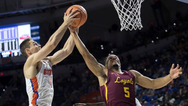 Florida guard Egor Koulechov, left, and Loyola-Chicago guard Marques Townes, right, battle for a rebound during the first half of their game Gainesville, Fla. on Wednesday.